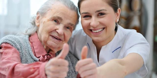 caretaker and elder woman doing a thumbs up