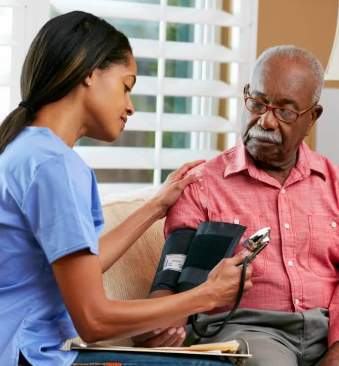 caretaker checking bp of elder man