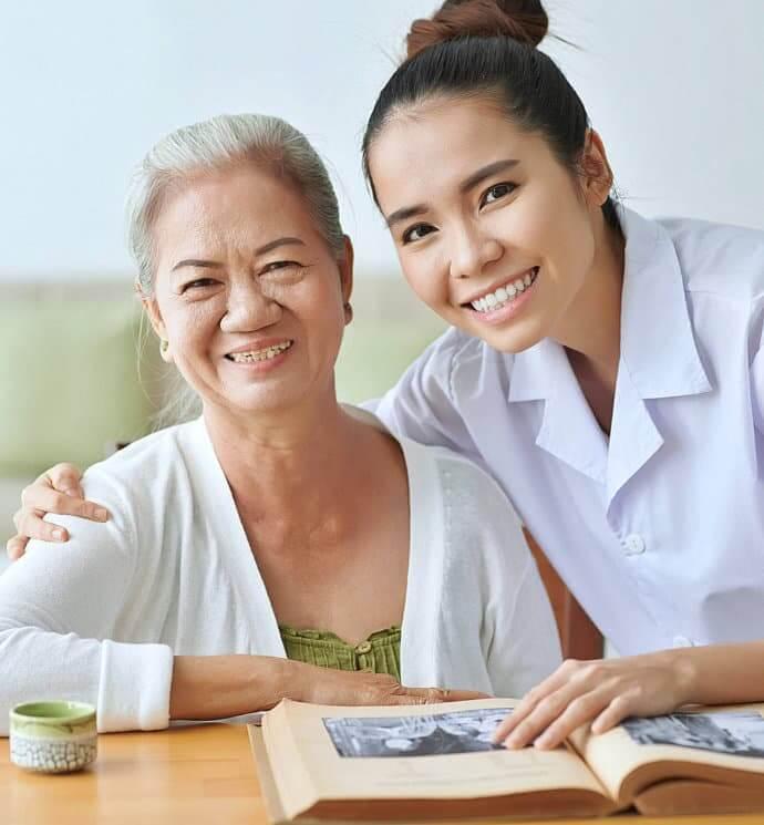 caretaker helping elderly read