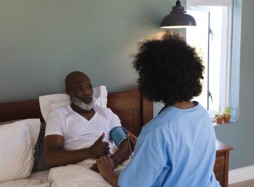 caregiver checking her patient blood pressure